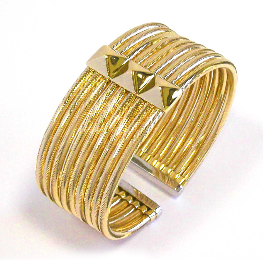 Nine rows of 18K yellow gold support a station with three pyramids with depth and dimension in this flexible cuff bracelet.