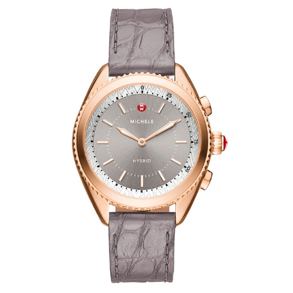 This hybrid smartwatch from Michele is beautiful and functional. The 38mm timepiece, crafted in rose gold plated stainless steel, has a sunray grey dial, a coin-edged bezel and grey alligator silicone strap. Use it to track your fitness, get notifications and alert vibrations, and take advantage of its ability to take pictures and play music. Get (and stay) connected with this Michele hybrid smartwatch!